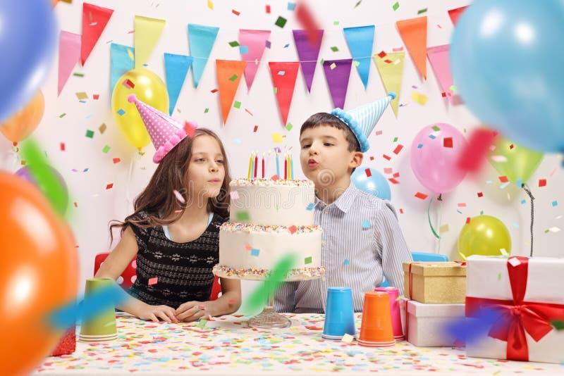 从生日蛋糕的女孩和男孩吹的蜡烛在党 免版税库存图片