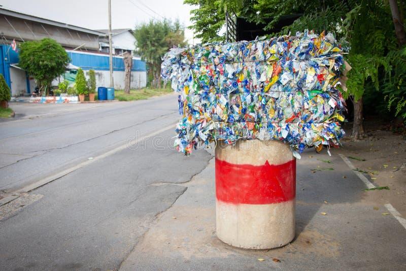 从用钢绳充塞的徽章或标签大块的垃圾在路旁混凝土被安置 库存照片