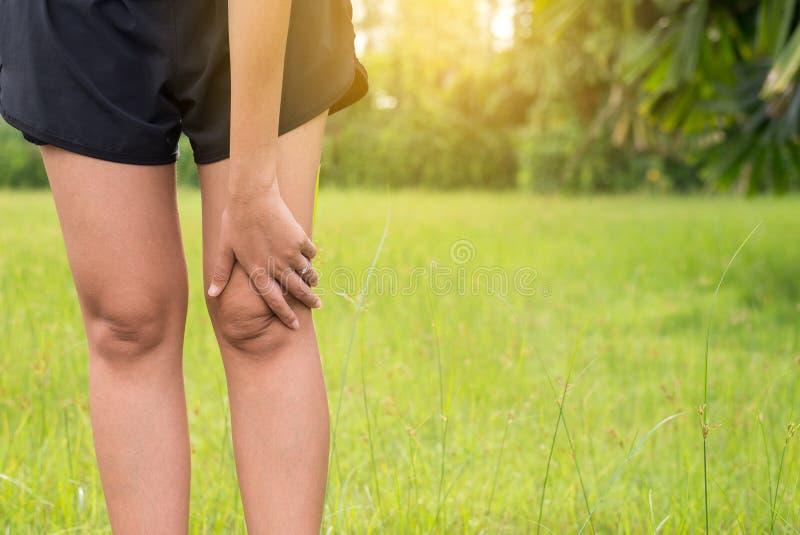 从痛苦的妇女痛苦在腿和膝盖受伤在体育跑步在公园的锻炼赛跑以后 库存图片