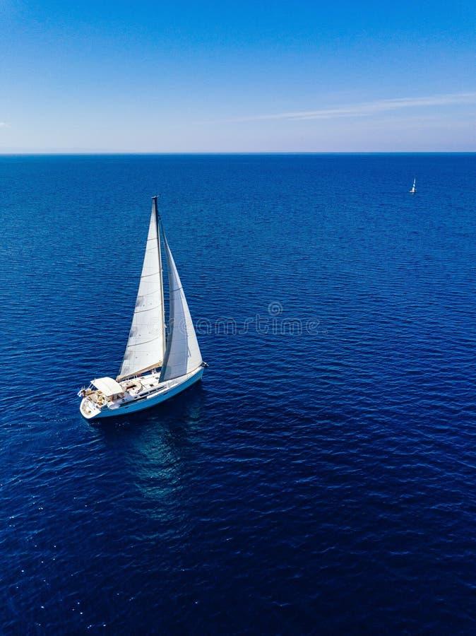 从白色游艇寄生虫的鸟瞰图在深蓝色海 免版税库存图片