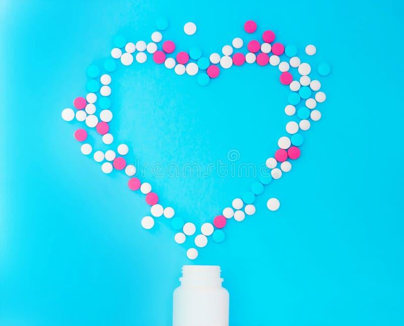 从白色瓶子的多彩多姿的药片在蓝色背景 免版税库存照片