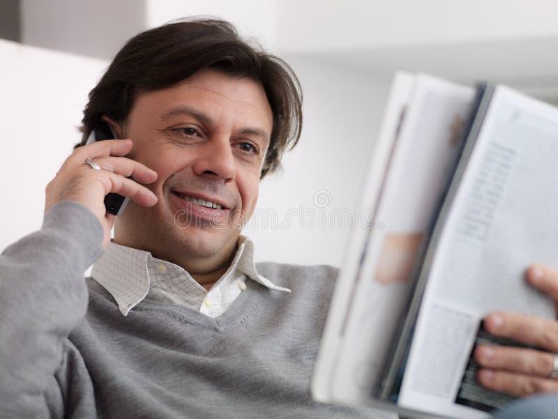 从目录的愉快的人购买与电话 免版税库存照片