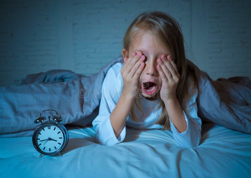 从看闹钟的失眠的女孩痛苦感觉绝望哀伤和不安定 库存图片
