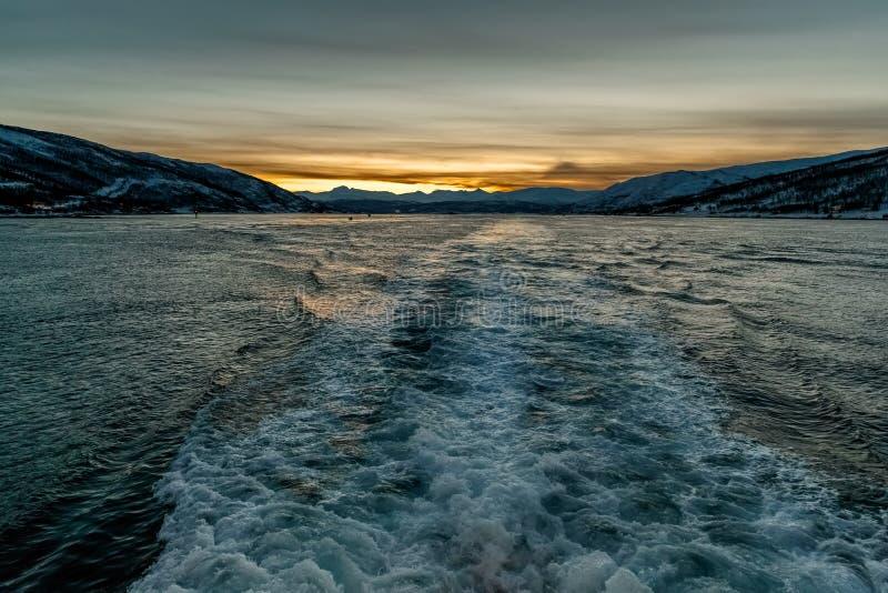 从移动的船的海视图到在山后的日落 图库摄影