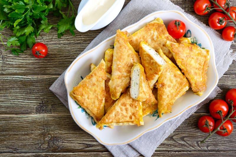 从稀薄的亚美尼亚lavash的鲜美油煎的吹小馅饼在一张木桌上 从皮塔饼面包酸奶干酪装填的信封 r 图库摄影
