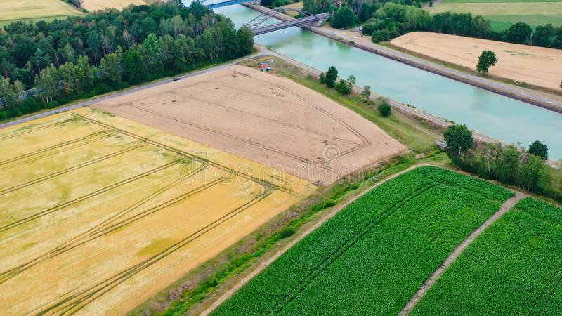 从空中看穿德国北部平地上穿过田地、草地和耕地的运河 免版税图库摄影