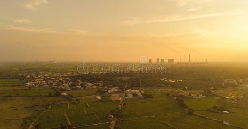 从空中观看煤电厂 — 在城市外的绿色农田附近的日出,印度赖舒尔 免版税图库摄影