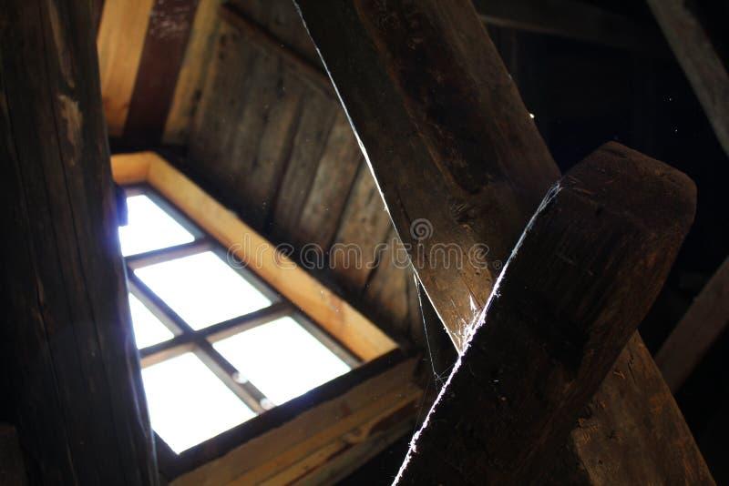 从窗口秋天的明亮的光在射线和蜘蛛网在一个老木房子里 免版税库存图片
