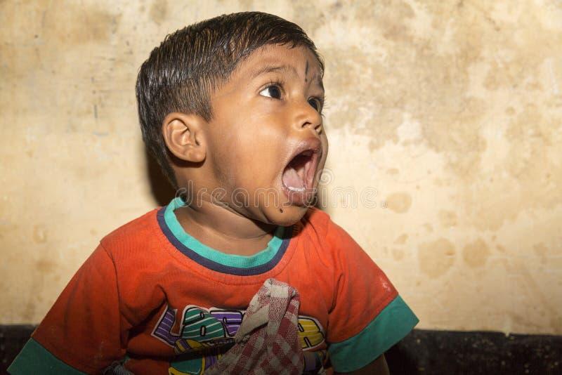从站立在streetside的印度的一个小叫化子男孩,哭泣为食物 库存照片