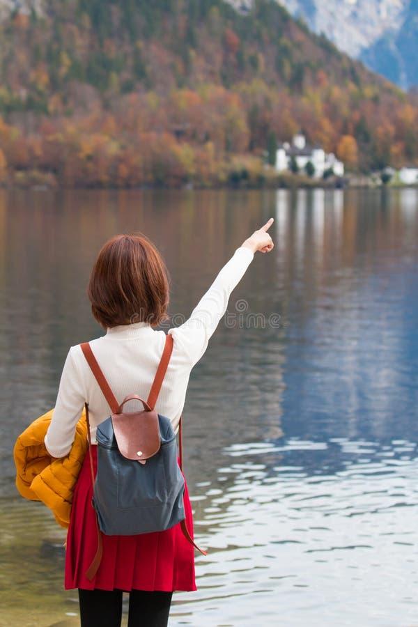 从站立的后面的亚裔旅游旅行家女孩把手指指向Hallstatt湖奥地利在秋天;平安的自由放松 免版税库存照片