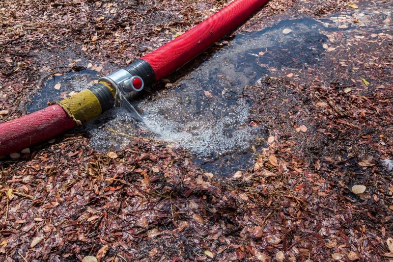 从管子漏的废水 漏的火管道联接 一个被爆裂的水管 配管残破的联接在孔用管道输送用水 免版税库存照片