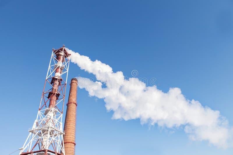 从管子的白色烟以天空为背景 库存照片