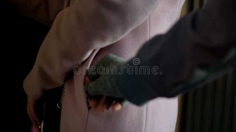 从粗心大意的女性通勤者口袋的犯罪窃取的金钱,pickpocketing 免版税库存图片