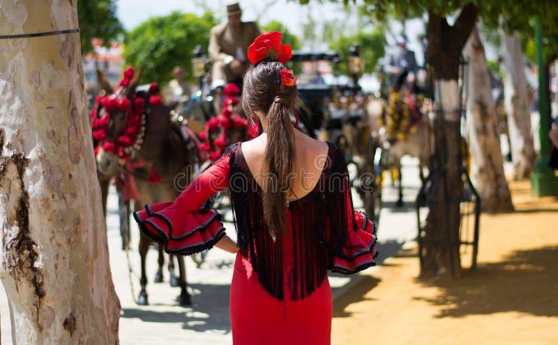 从红色佛拉明柯舞曲礼服的女孩在塞维利亚,公平的4月的 免版税库存照片