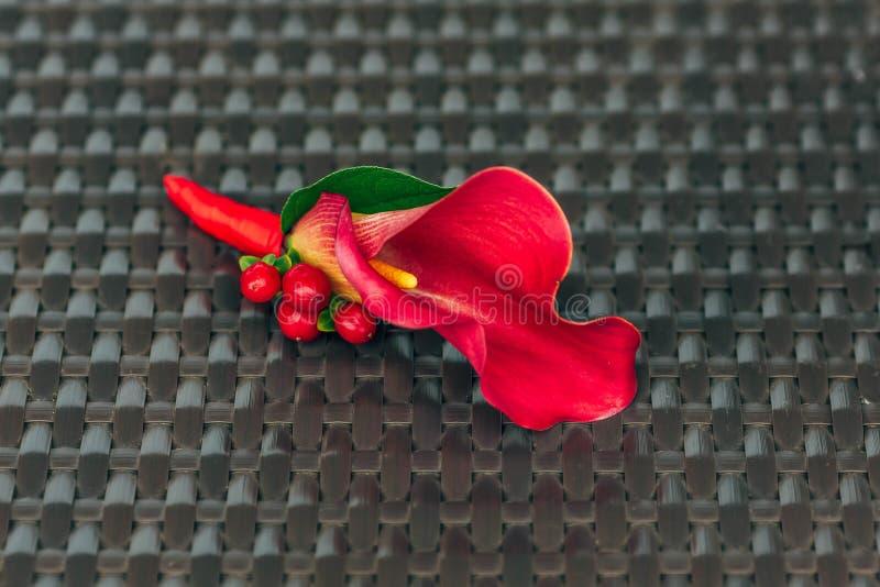 从红色水芋属的婚礼钮扣眼上插的花在棕色柳条纹理 特写镜头 附庸风雅 免版税库存照片