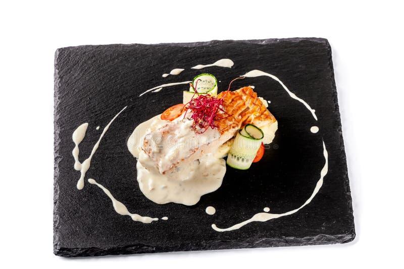 从红色鱼三文鱼或鳟鱼的鱼排,与土豆泥、西红柿、黄瓜和乳脂状的调味汁小菜  免版税库存图片