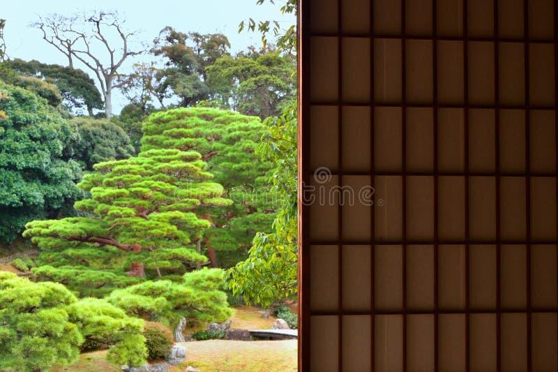 从纸窗口,日本的平安的日本庭院 图库摄影