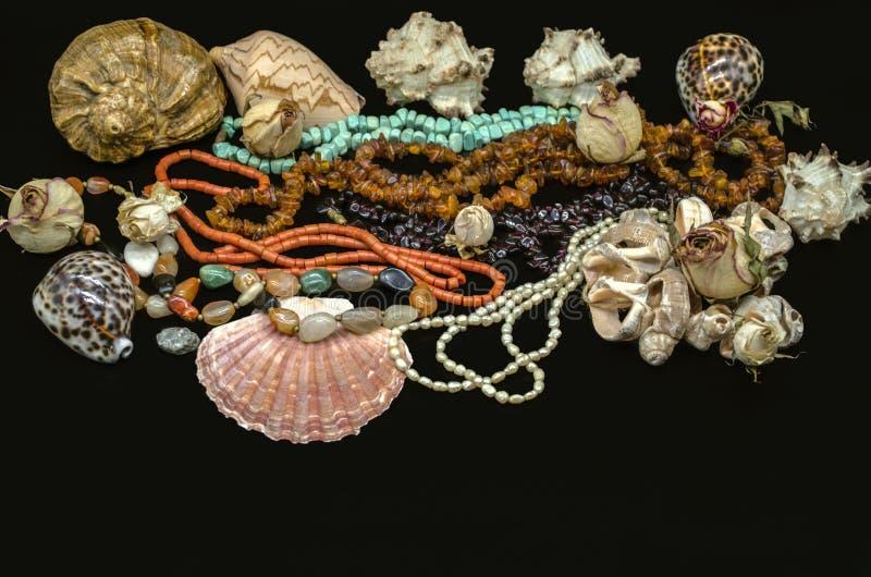 从绿松石,红珊瑚,琥珀,石榴石,五颜六色的玛瑙,与贝壳的珍珠的美丽的小珠在黑背景 免版税库存照片