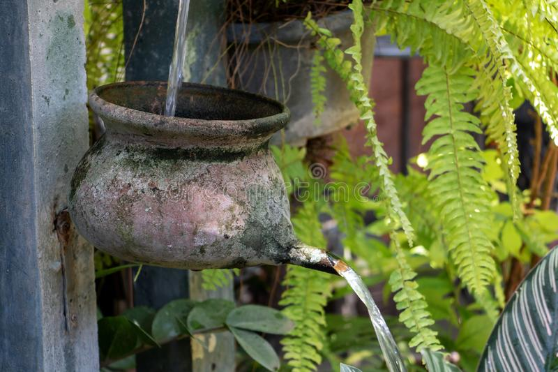从罐的水小瀑布在与流动的水的柱子 免版税库存图片