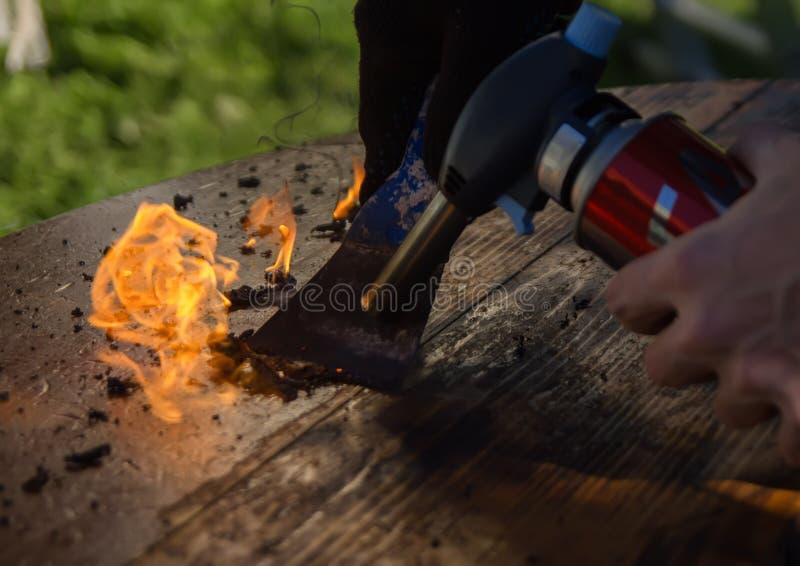 从老油漆的清洁工作台面与火 木材加工,老家具的恢复 图库摄影