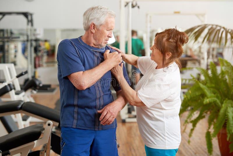 从肩膀痛苦的老人痛苦在健身房 免版税库存照片
