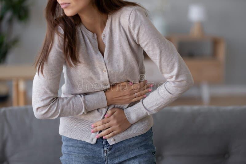 从胃痛的年轻病态的妇女身分藏品腹部痛苦 免版税库存照片