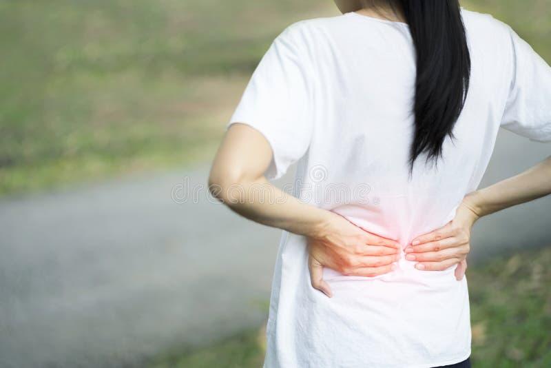 从背部疼痛的年轻女人痛苦,当走为锻炼在公园,健康概念时的伤害 免版税库存图片