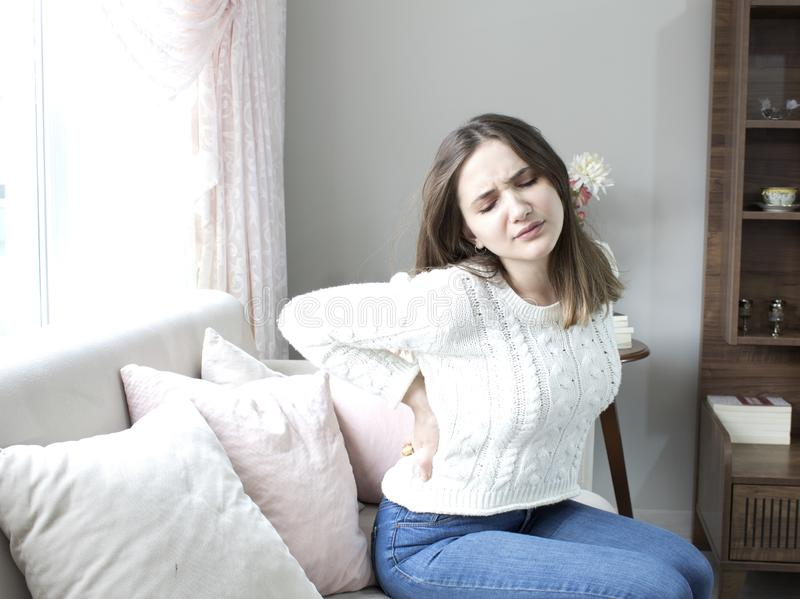 从腰疼的美好的年轻女人痛苦在家 免版税库存照片
