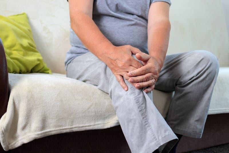 从膝盖痛苦坐的沙发的老人痛苦 免版税库存照片