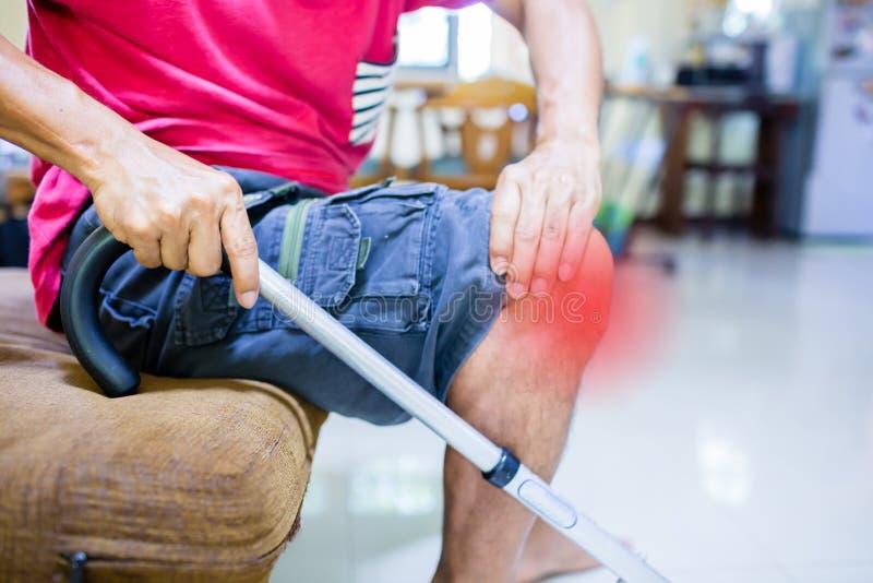 从膝盖痛苦的人痛苦和在沙发的拐棍开会 免版税图库摄影