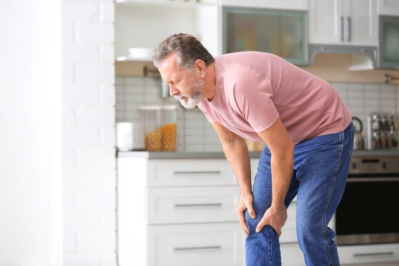 从膝盖痛苦的老人痛苦在厨房里 免版税库存图片
