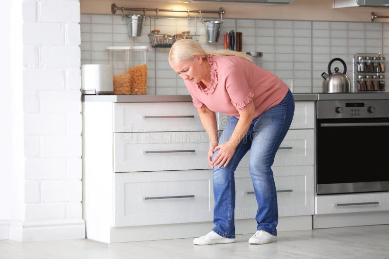 从膝盖痛苦的资深妇女痛苦在厨房里 图库摄影