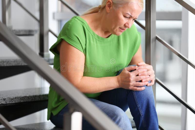 从膝盖痛苦的资深妇女痛苦 库存照片