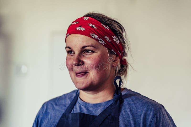 从膳食准备的女性厨师休假-愉快,微笑,努力人的概念 免版税图库摄影