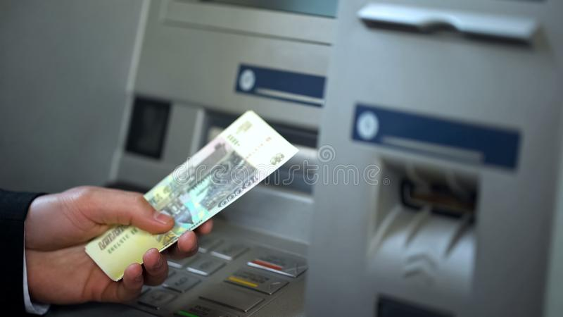 从自动出纳机的男性得到的俄罗斯卢布,现金让步 库存图片