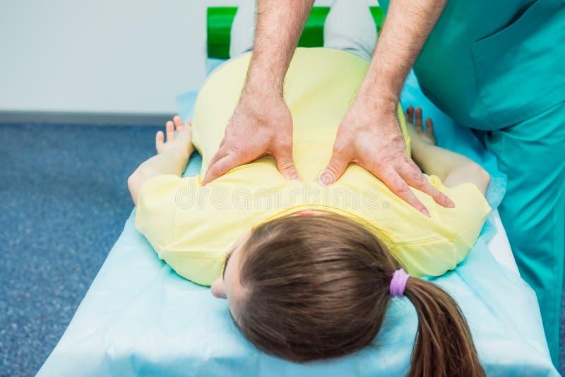 从舒展他的耐心` s脊椎的治疗师A按摩医生的年轻女性接受按摩在医疗办公室 神经学phys 库存照片