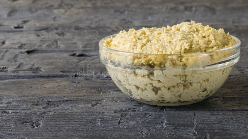 从芝麻籽的新鲜的面团tahini与橄榄油和柠檬汁在黑木桌上 免版税库存图片