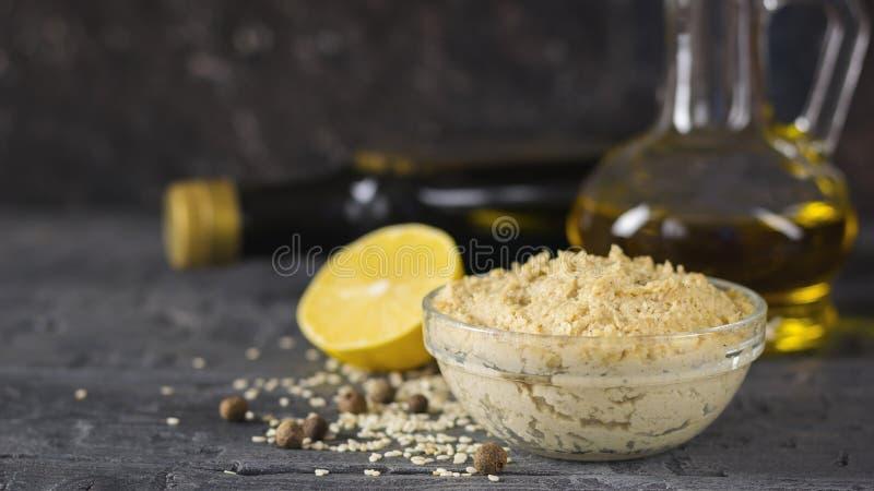 从芝麻籽的新鲜的面团tahini与橄榄油和柠檬汁 免版税库存照片