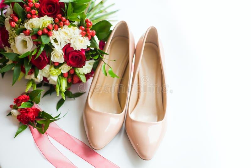 从花和新娘` s鞋子花束的静物画在白色背景 免版税库存照片