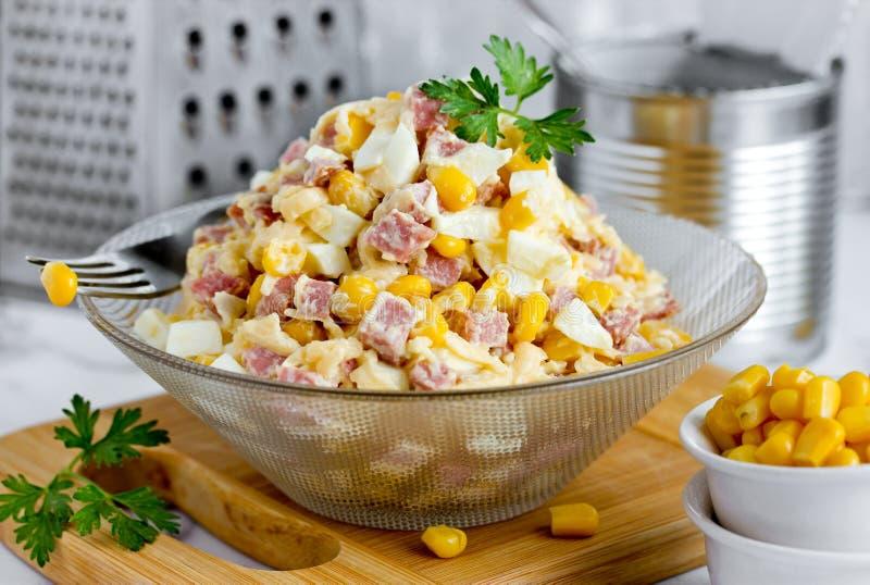 从蒜味咸腊肠香肠、乳酪、熟蛋和罐装玉米的凉拌生菜 图库摄影