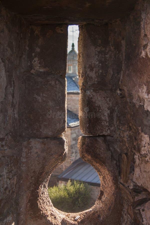 从蓬费拉达城堡墙壁的发射孔看见的圣安德列斯教会  免版税库存照片