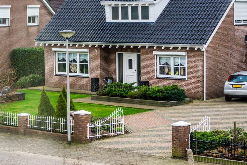 从街道视图的豪华荷兰平房,与美丽的庭院和门,现代荷兰建筑学,家在一个小村庄  免版税库存图片