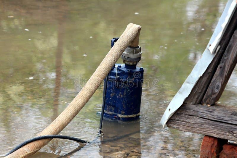 从被充斥的后院的深蓝被毁坏的老部分地被淹没的金属水泵抽的洪水通过大直径 图库摄影