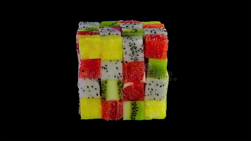 从被分类的热带水果小正方形形成的果子立方体在一个五颜六色的安排的包括猕猴桃,草莓,桔子 库存图片