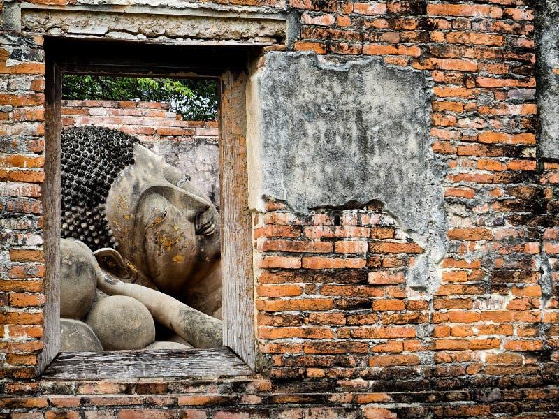 从被破坏的古庙的窗口的巨型斜倚的菩萨景色 免版税库存照片