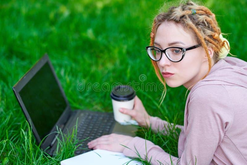 从设备的自由职业者妇女:膝上型计算机、片剂、说谎在草和工作的球员、笔记本和咖啡 库存照片