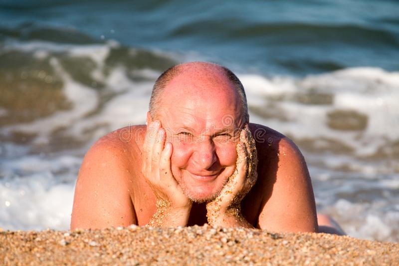 从说谎在海泡沫的沙子和取暖在波浪的太阳的年长人半眯着的眼睛 图库摄影