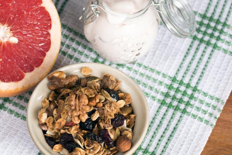 从谷物的几种类型的格兰诺拉麦片与坚果、椰子削片和干蔓越桔的 瓶子用自创酸奶和葡萄柚 库存图片