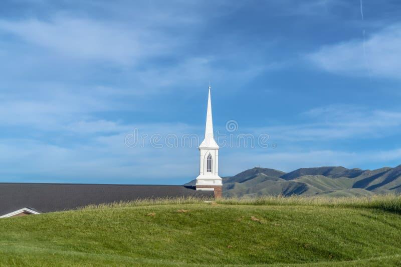 从象草的小山观看的教会的白色尖顶和屋顶在一好日子 库存图片