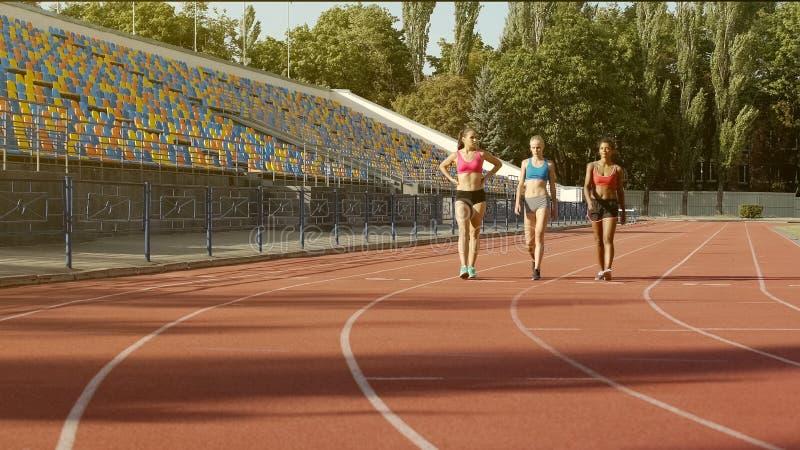 从走向体育训练的国家队的三个美丽的多种族女孩 库存图片